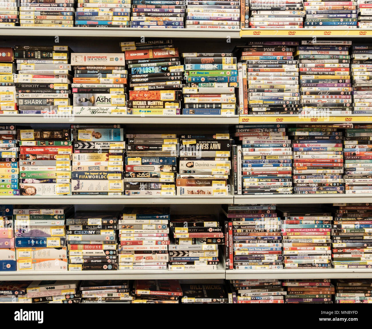 DVD`s and videos stacked on shelfs in Cash Converters pawnbrokers. UK - Stock Image