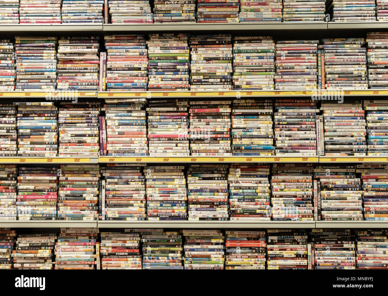 DVD`s stacked on shelfs in Cash Converters pawnbrokers. UK - Stock Image