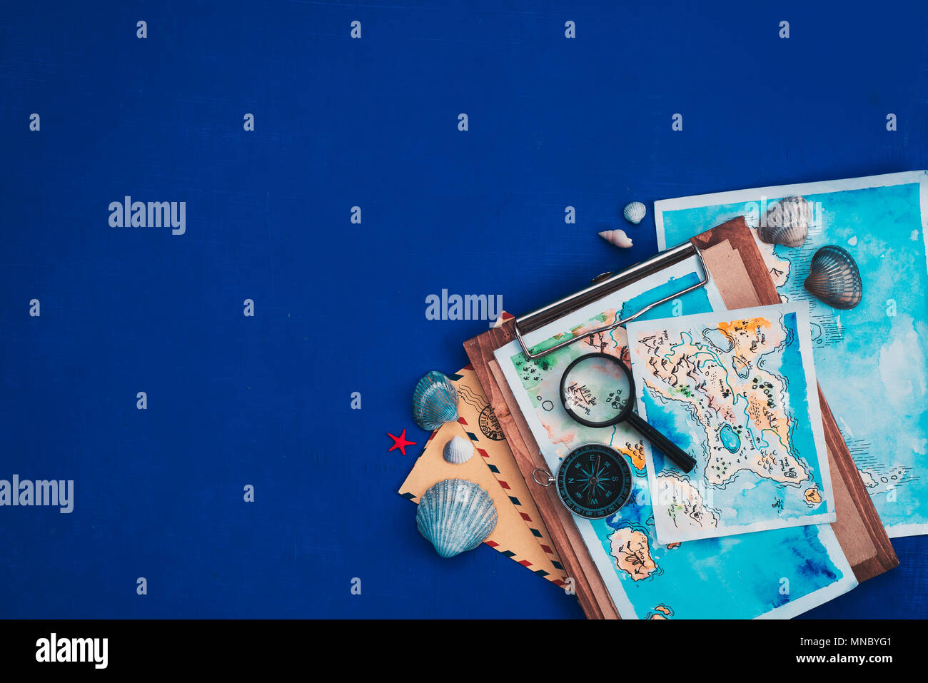 Sea travel and exploration concept. Watercolor maps on a wooden clipboard, compass and magnifying glass flat lay on a navy blue background with copy s - Stock Image