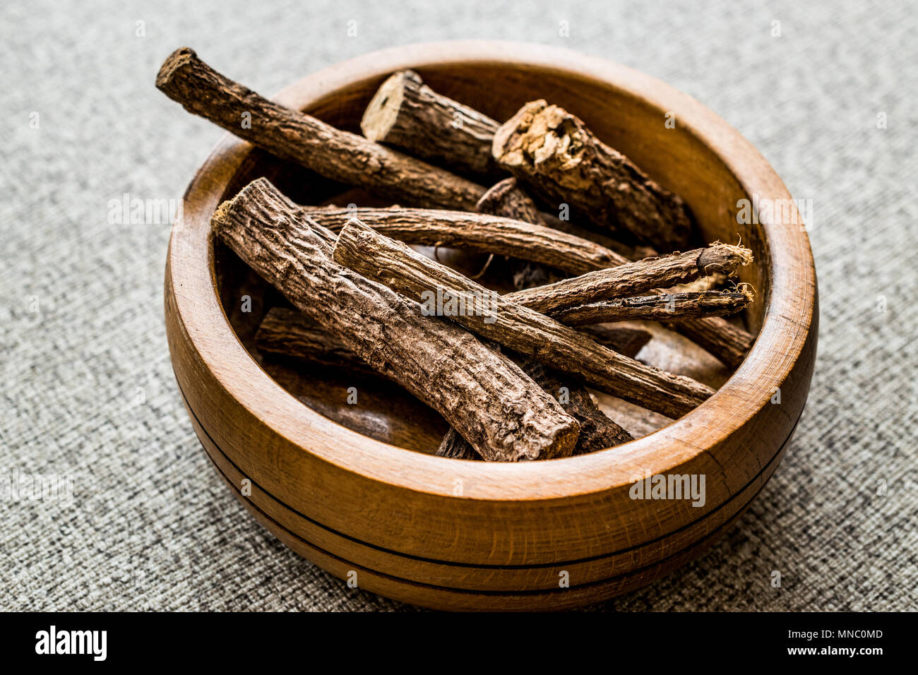 Dried Licorice Sticks in wooden bowl / Meyan Koku. Organic Concept. - Stock Image