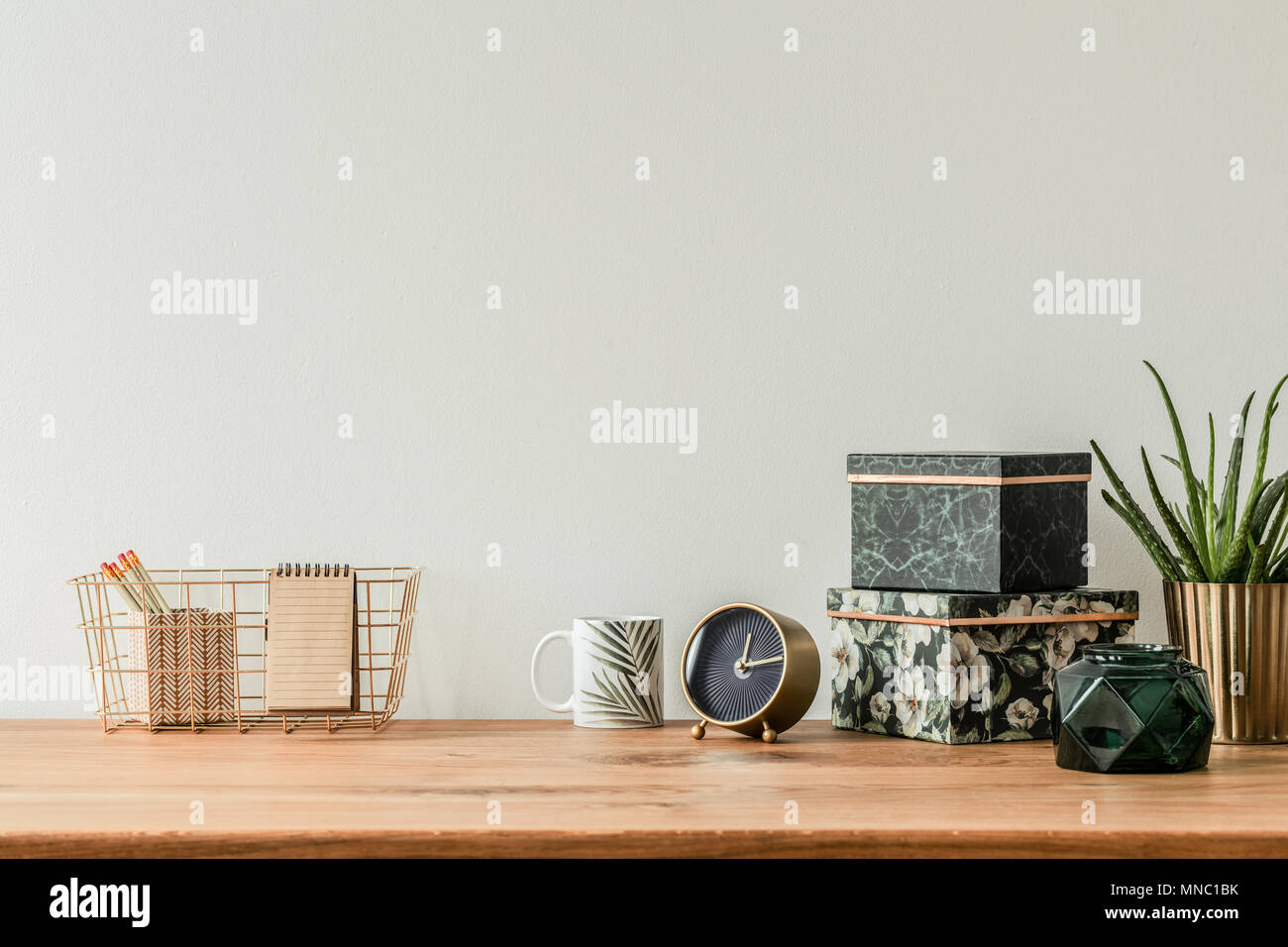 Organized table top with floral boxes, mug, clock and metal box on an empty wall Stock Photo