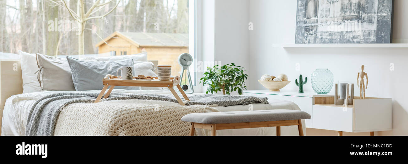 Header of a bright bedroom interior with large window and white furniture - Stock Image