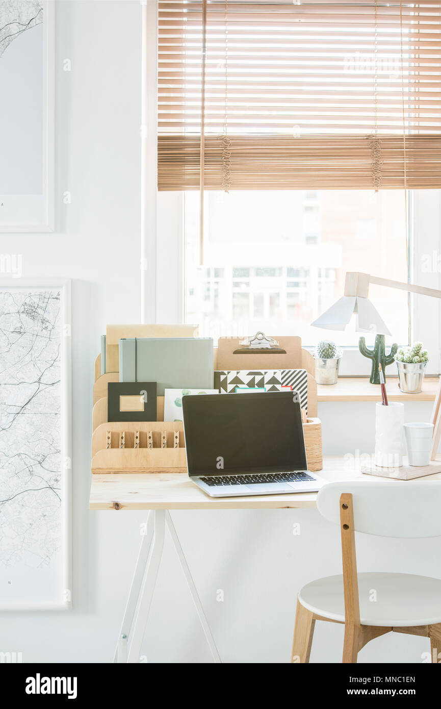 White chair at desk with laptop and wooden organizer in natural home office interior with window - Stock Image