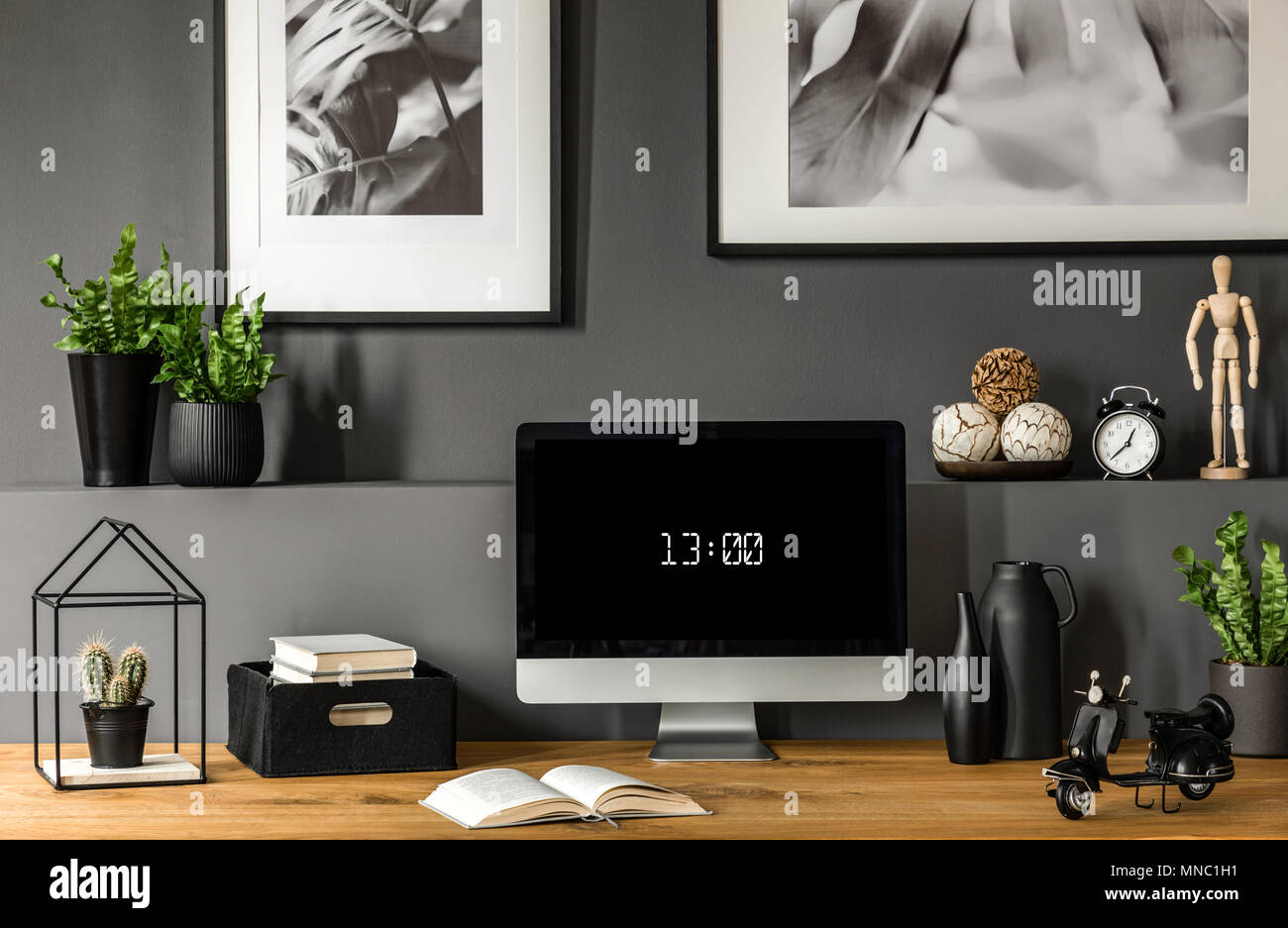 Close-up of wooden workspace with computer monitor showing the time below botanic, black and white posters. Real photo - Stock Image