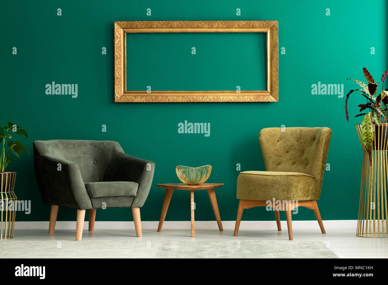 Gold Frame Hanging On The Wall In Green Interior With Two Armchairs
