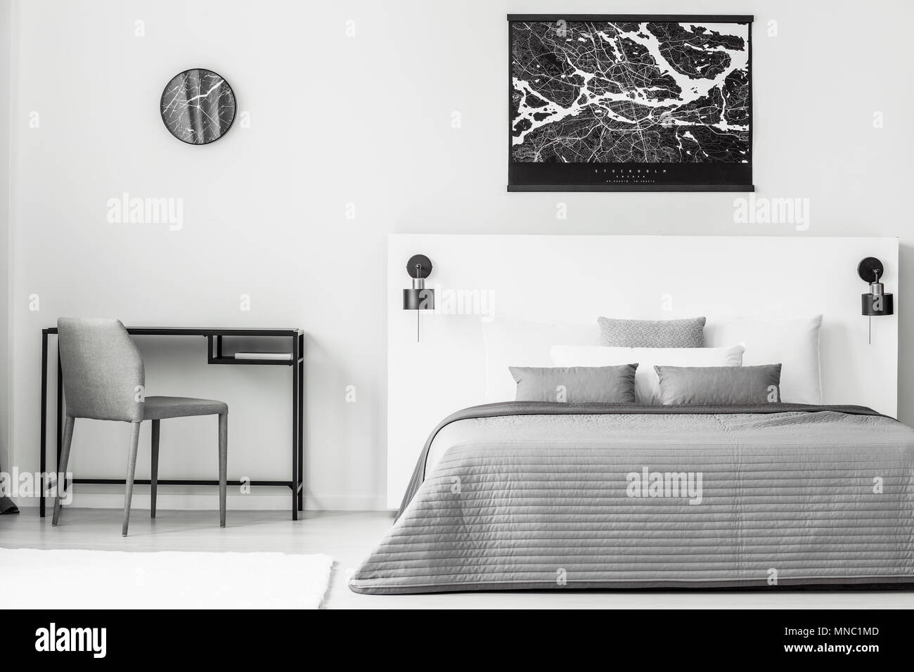 Black poster above grey and white bed in bedroom interior ...