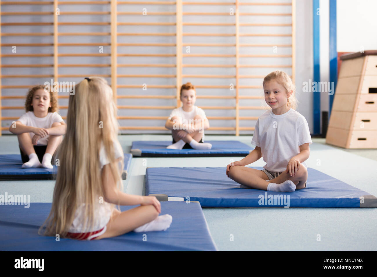 Happy young girls sitting across from each other on blue exercising mats with their legs crossed during PE classes in the primary school gym interior Stock Photo