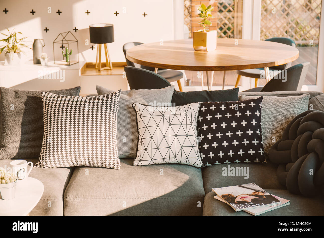 Black And White Decorative Pillows On A Gray Sofa In A Sunlit Living Room Interior With A Wooden Dining Table Stock Photo Alamy