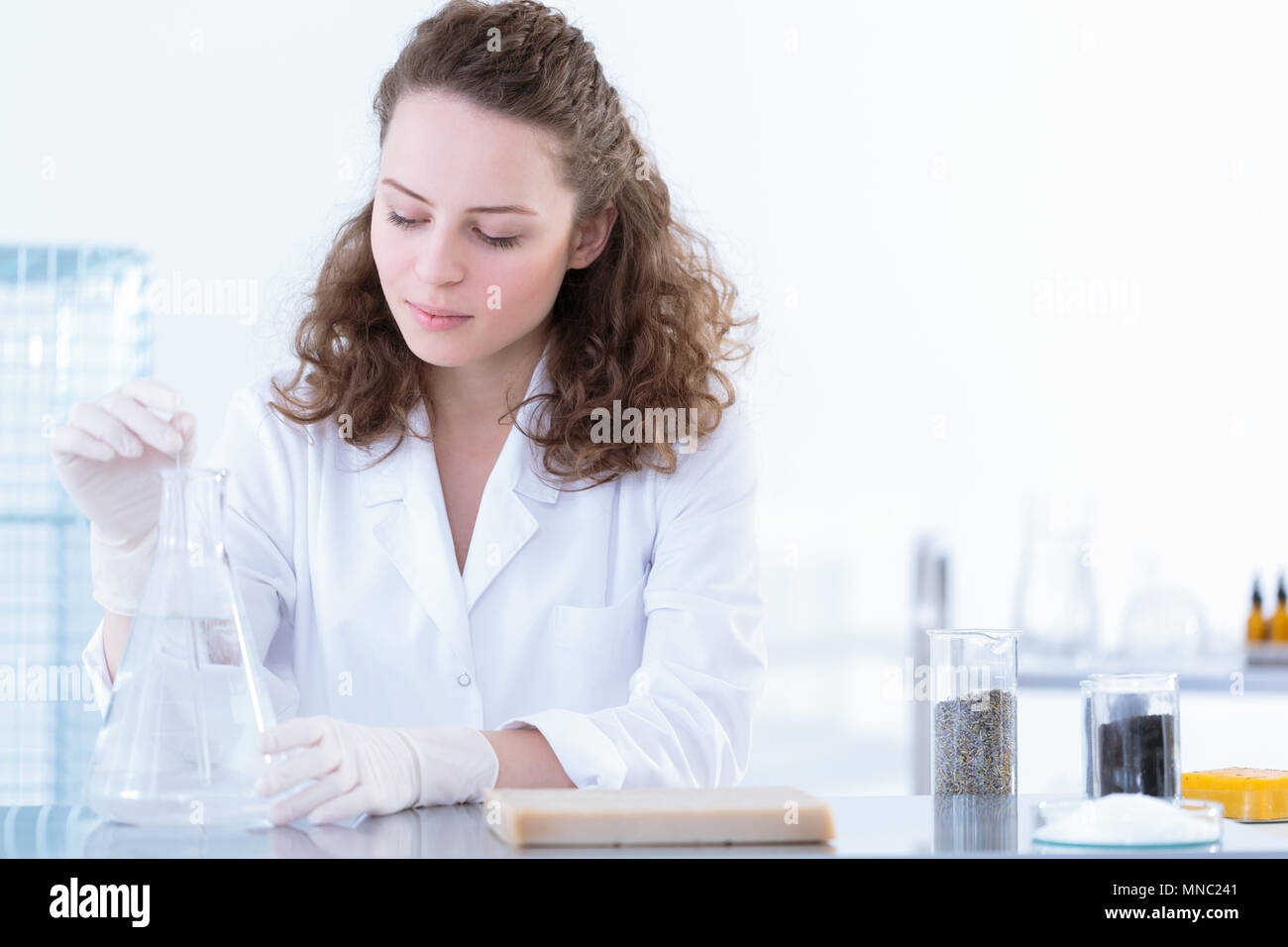 Biotechnologist dissolving the sample in a solution during laboratory analysis - Stock Image