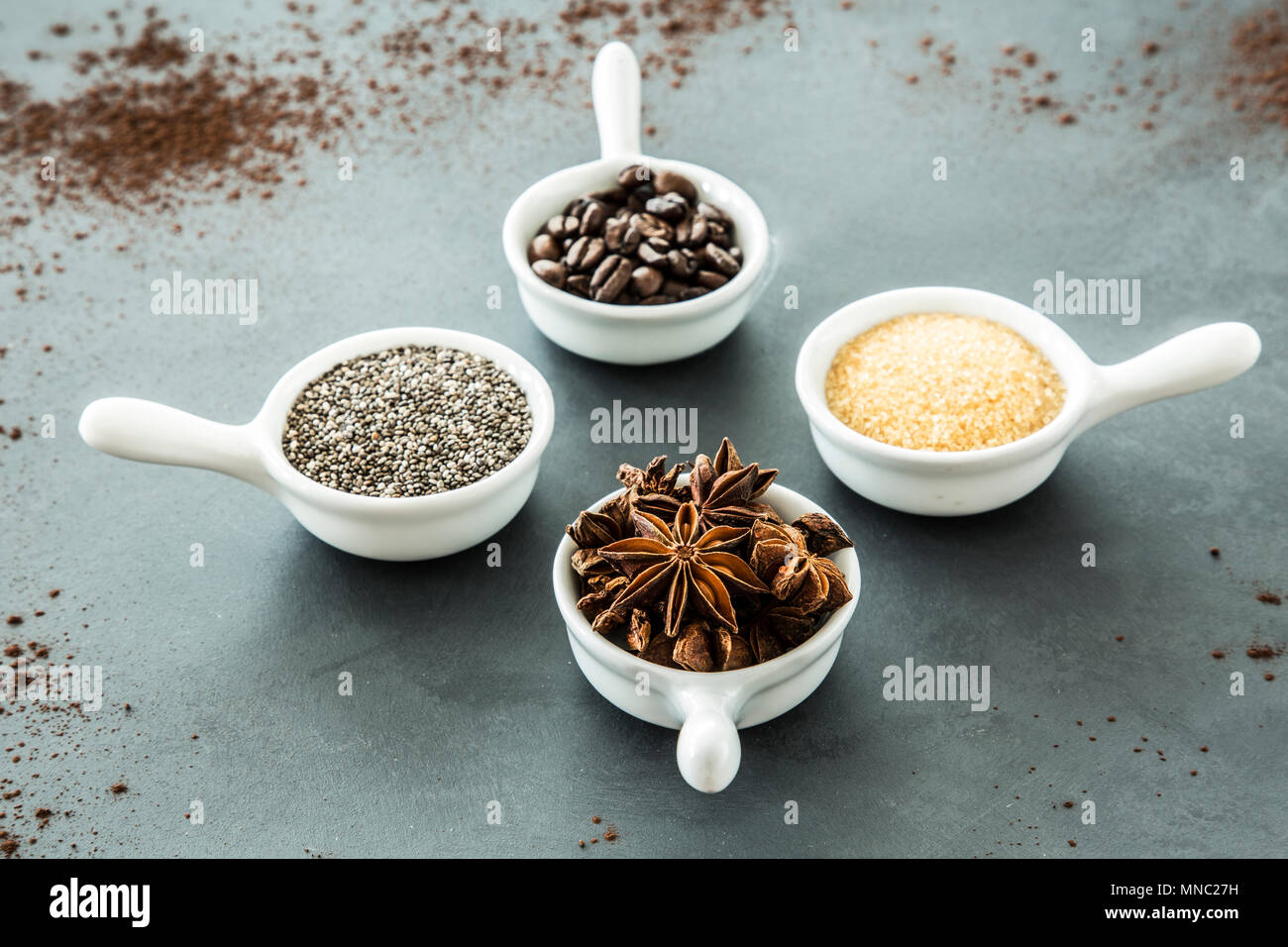 Coffee beans, seeds and star anise in small, matching bowls on a gray table. Concept of flavoring food - Stock Image