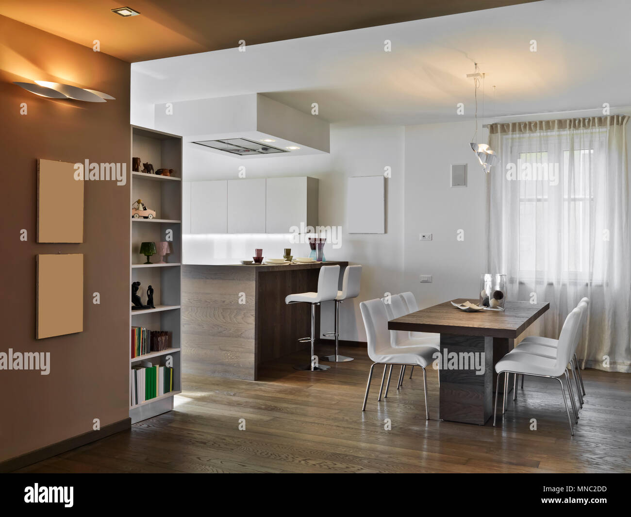 interiors shots of a modern apartment in the foreground the wooden dining table and his fabric chairs on the background - Stock Image