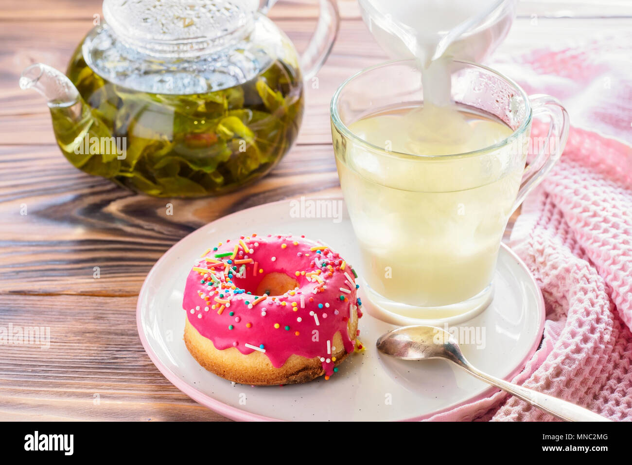 Cup of hot green tea beverages with donut glazed - Stock Image