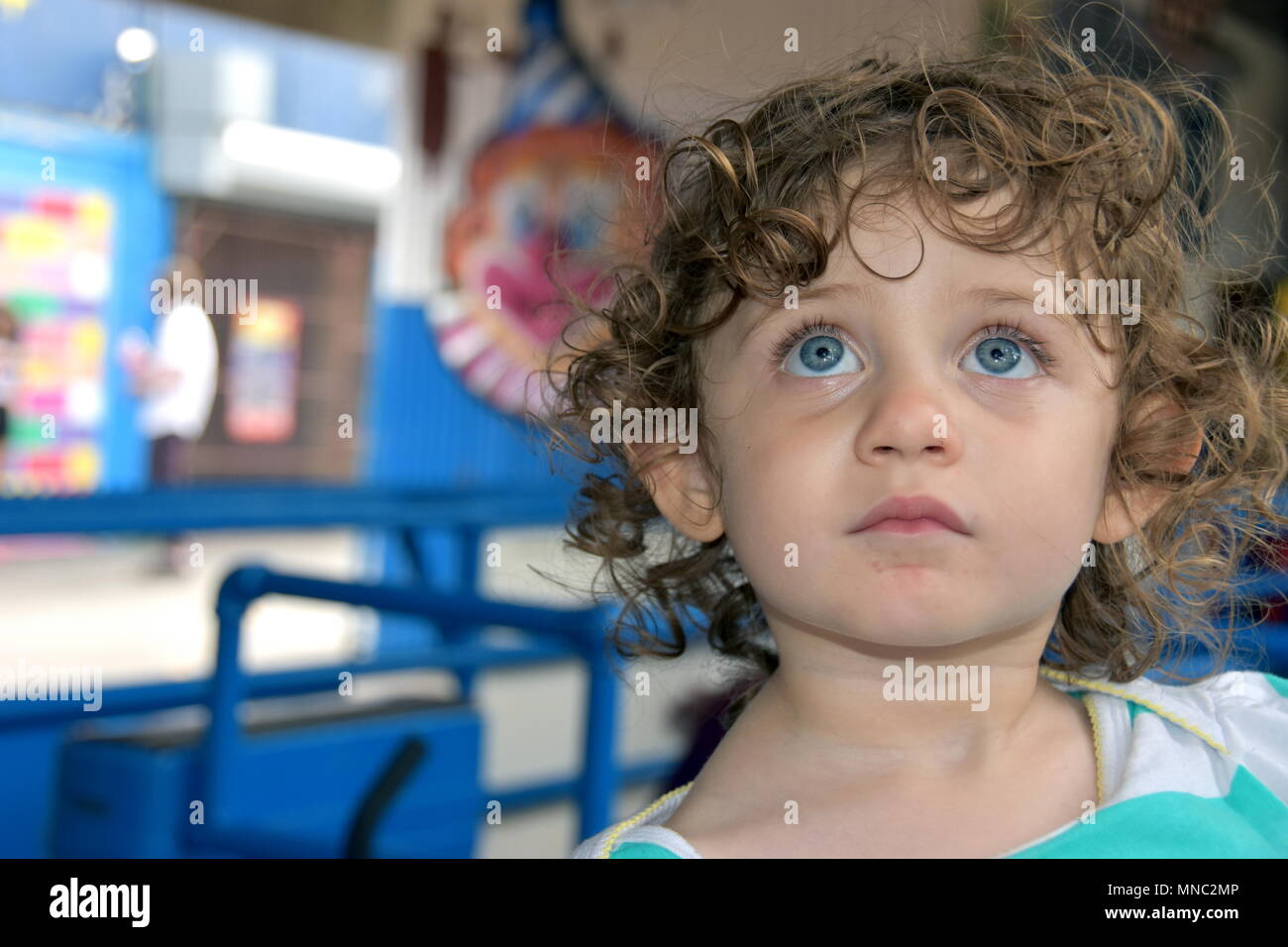 Beautiful little girl stares up at an amusement park ride while waiting below in the line - Stock Image