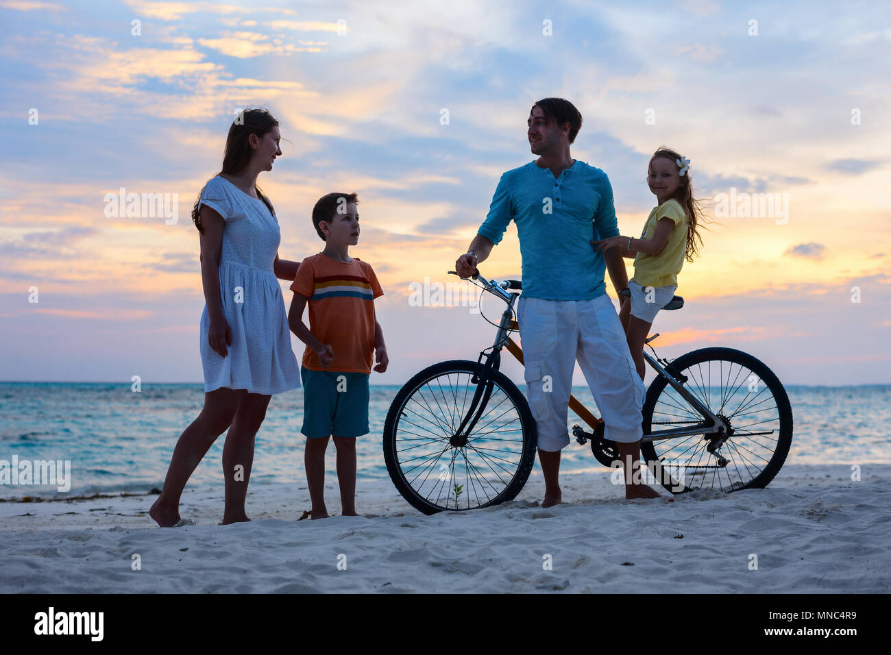 Family with a bike on tropical beach during sunset - Stock Image