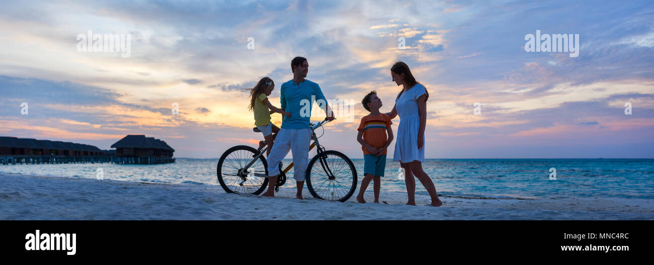Family with a bike on tropical beach at sunset, Stitched Panorama - Stock Image
