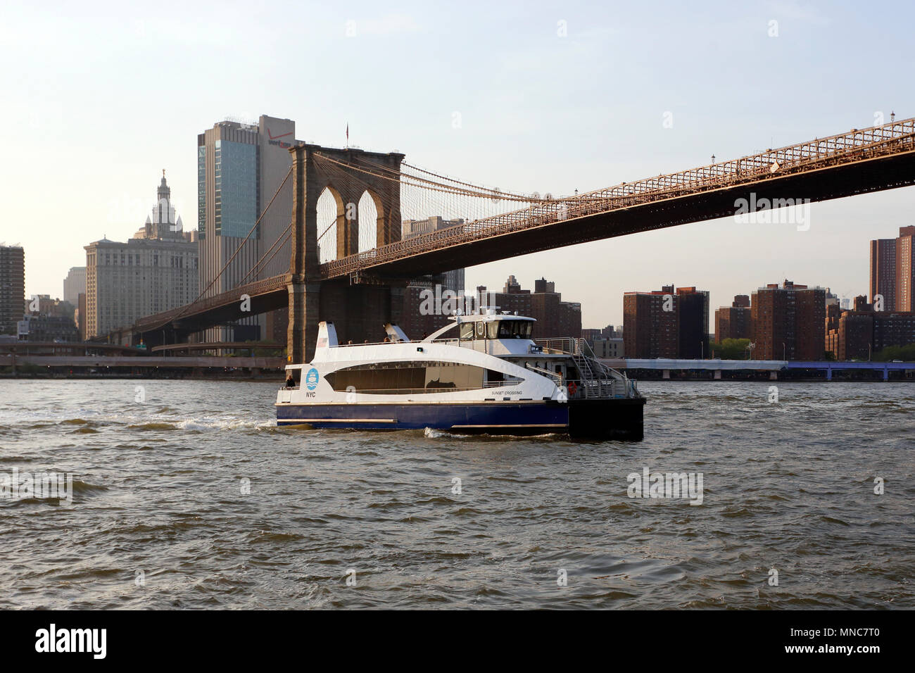 NYC Ferry Boat 'Sunset Crossing' crossing the East River at sunset - Stock Image