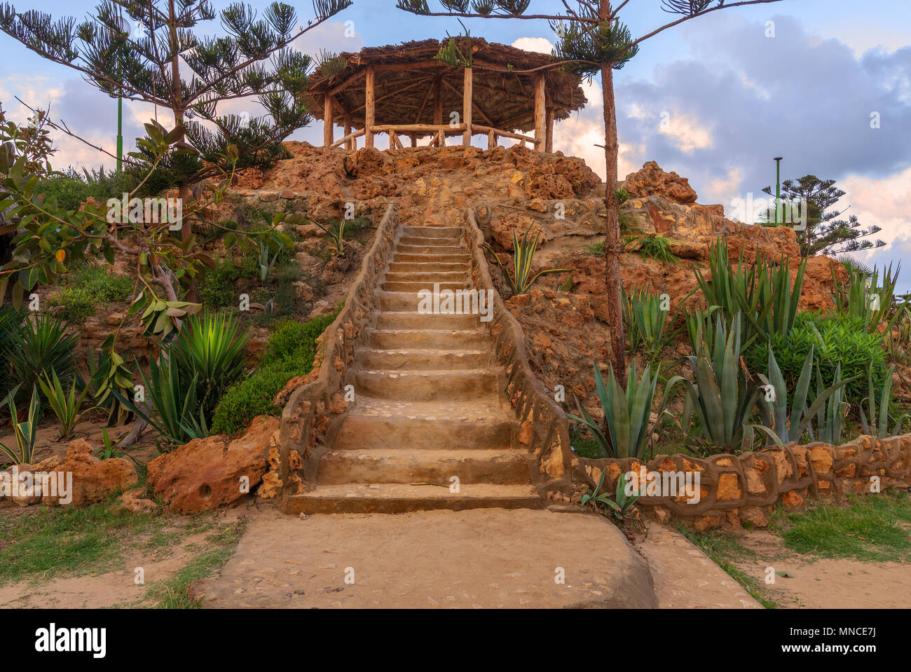 Natural stone stairway with green bushes on both sides leading to wooden pergola with partly cloudy sky at Montaza Park in summer time, Alexandria, Eg - Stock Image