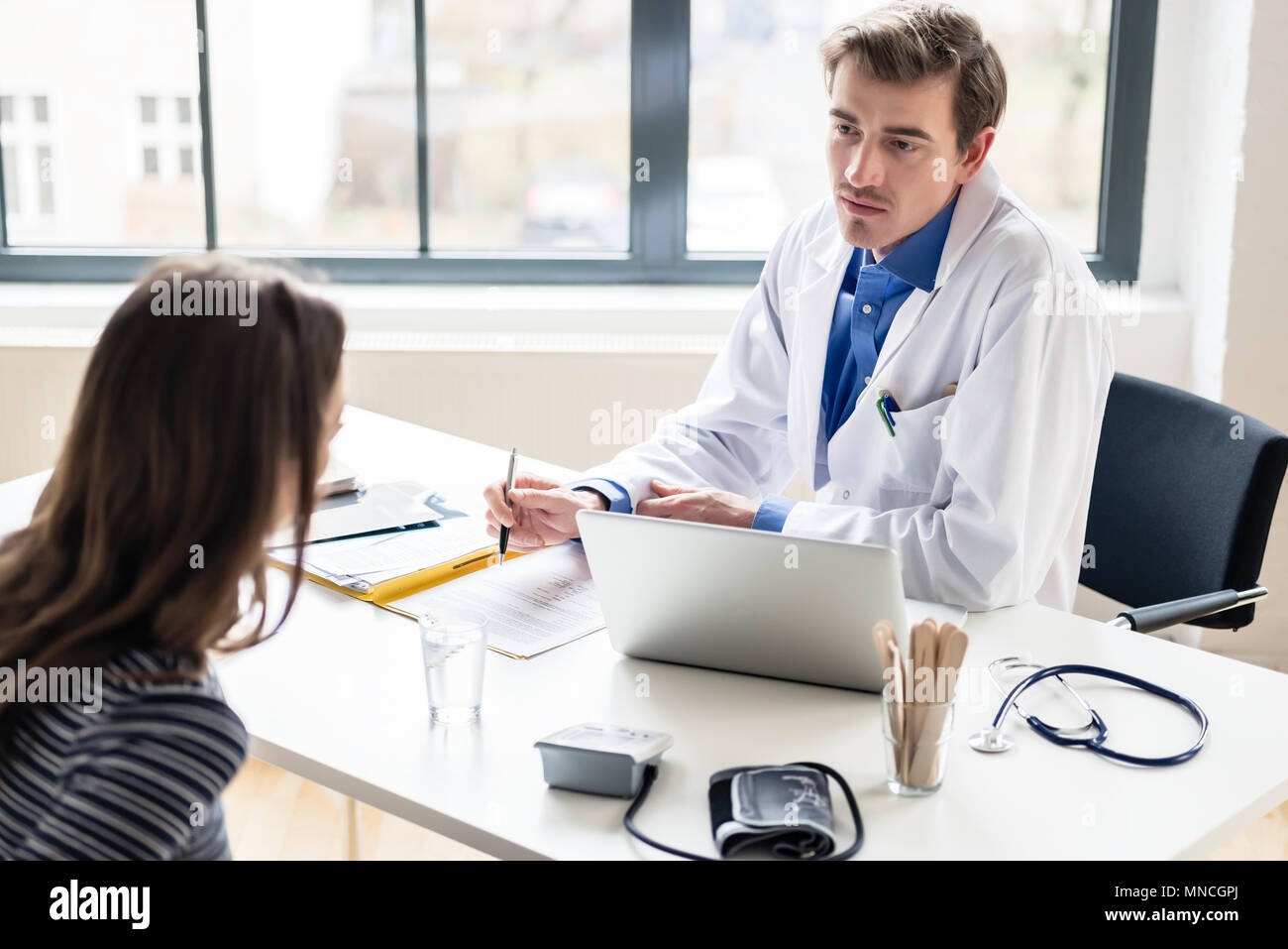 Young physician listening to his patient with respect and dedication - Stock Image