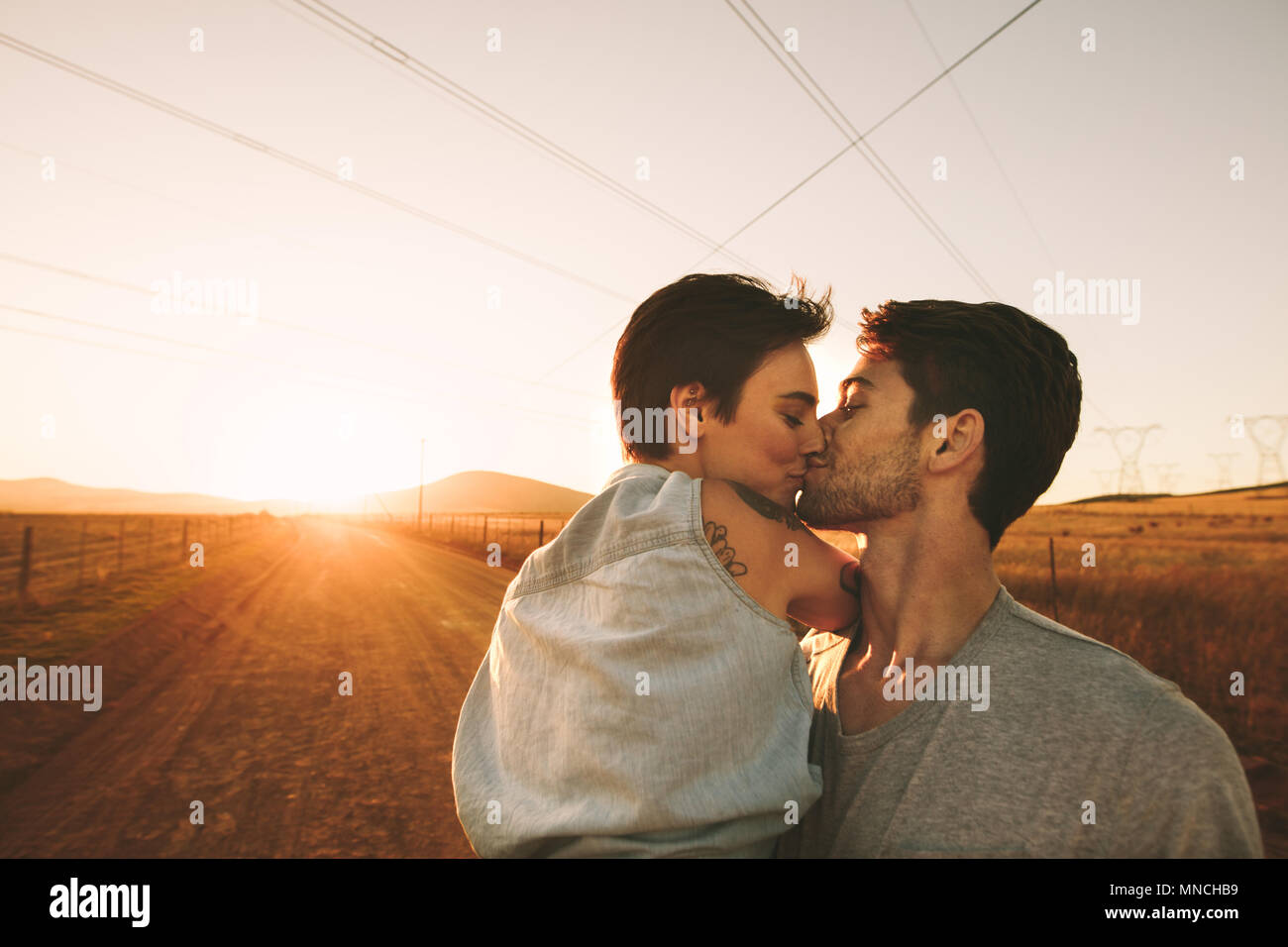 Couple kissing on a mud track highway in countryside. Romantic couple on the highway spending time together. - Stock Image