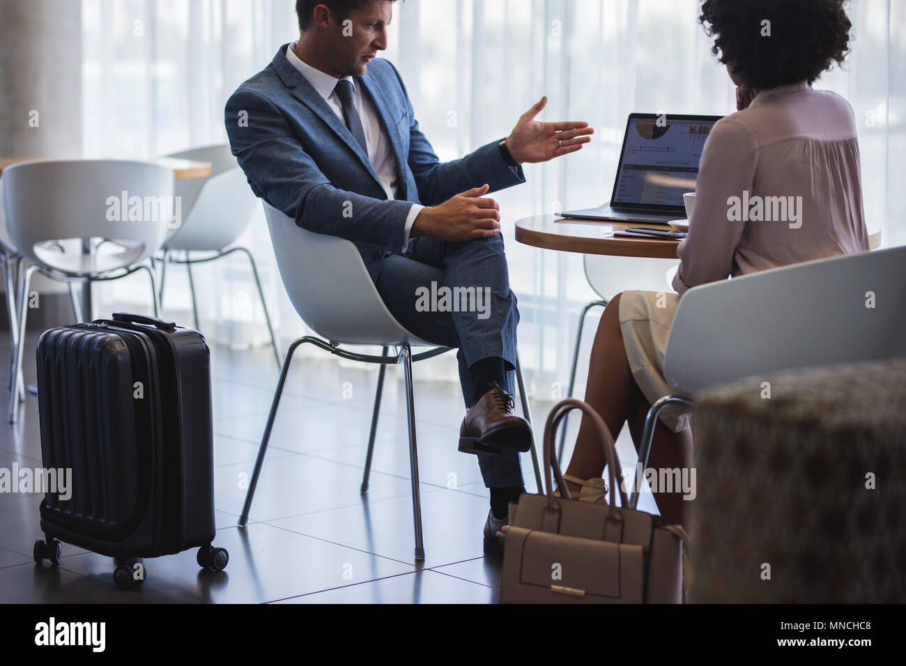 Business man showing something to woman while sitting at airport lounge. Business people working on laptop while waiting for their flight. - Stock Image