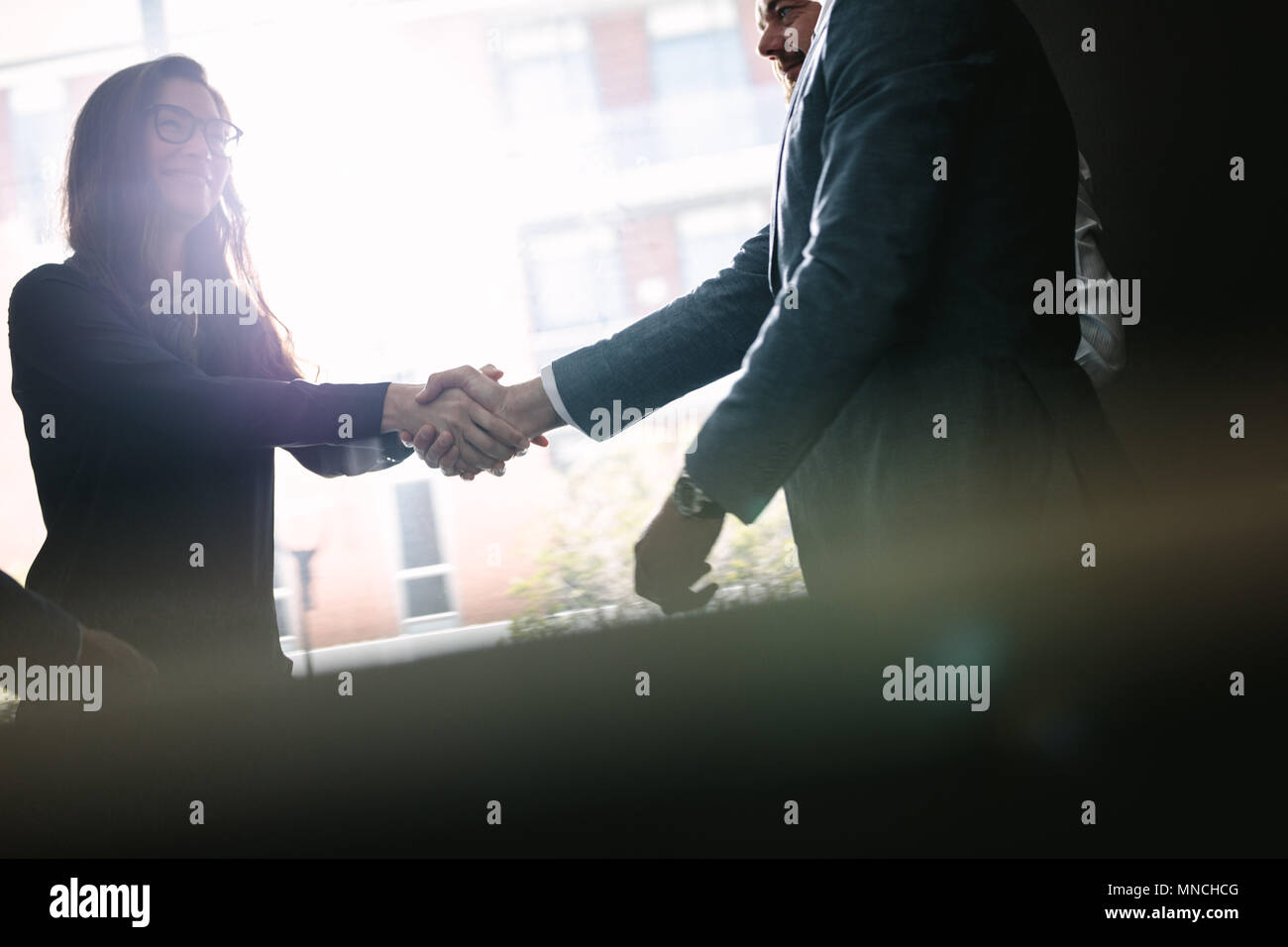 Businesswoman shaking hands with businessman after a successful agreement in office meeting. Businesspeople hand shake after a deal. - Stock Image