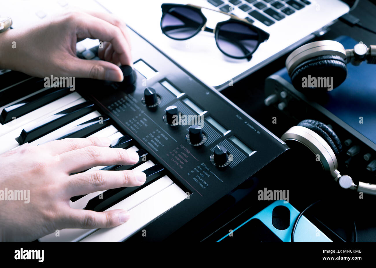 Music producer is producing Music on synthesizer keyboard - Stock Image