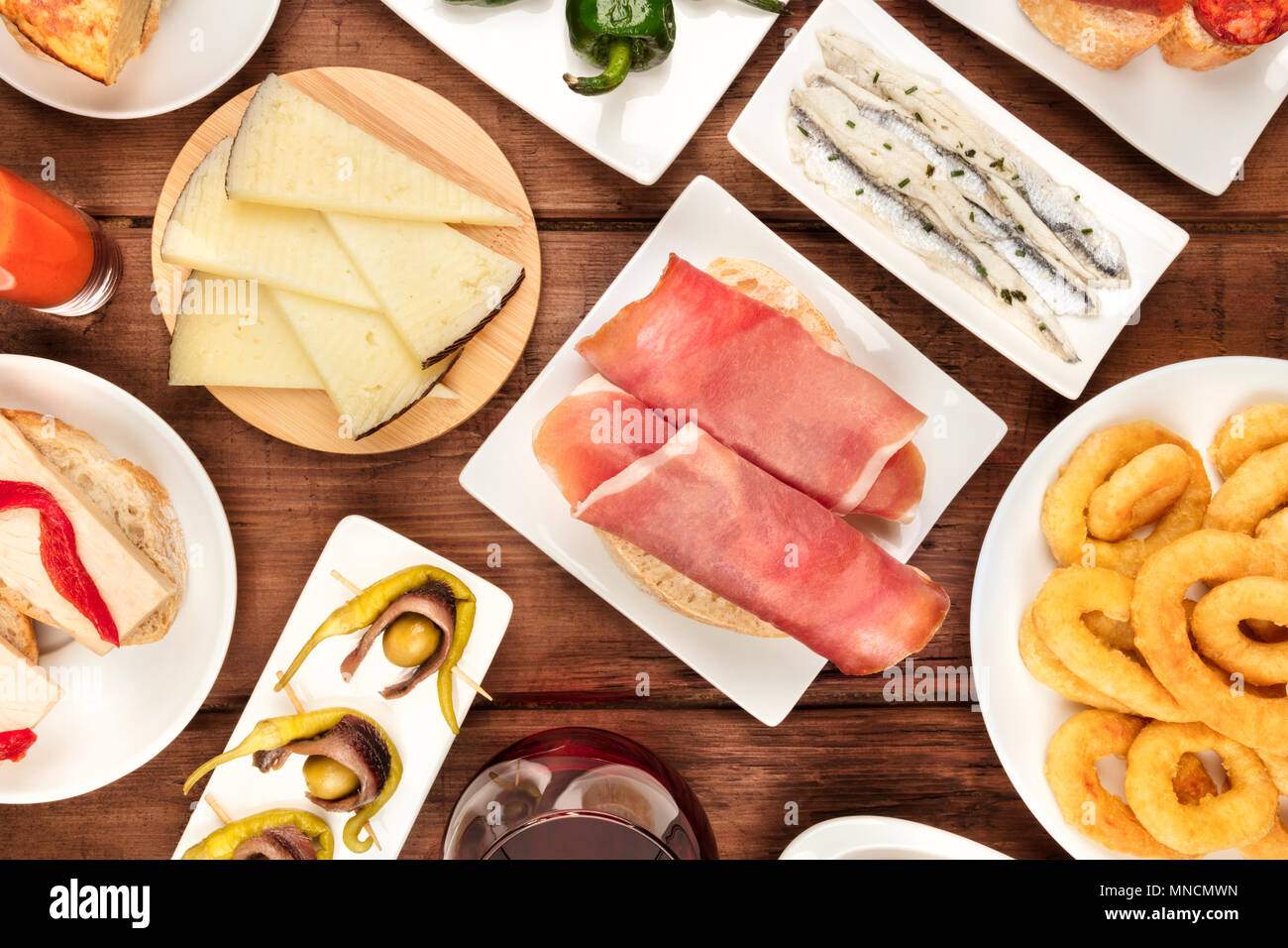 The food of Spain. An overhead photo of different Spanish tapas, shot from above on a dark rustic texture. Jamon, cheese, gildas, anchovies, calamari  - Stock Image