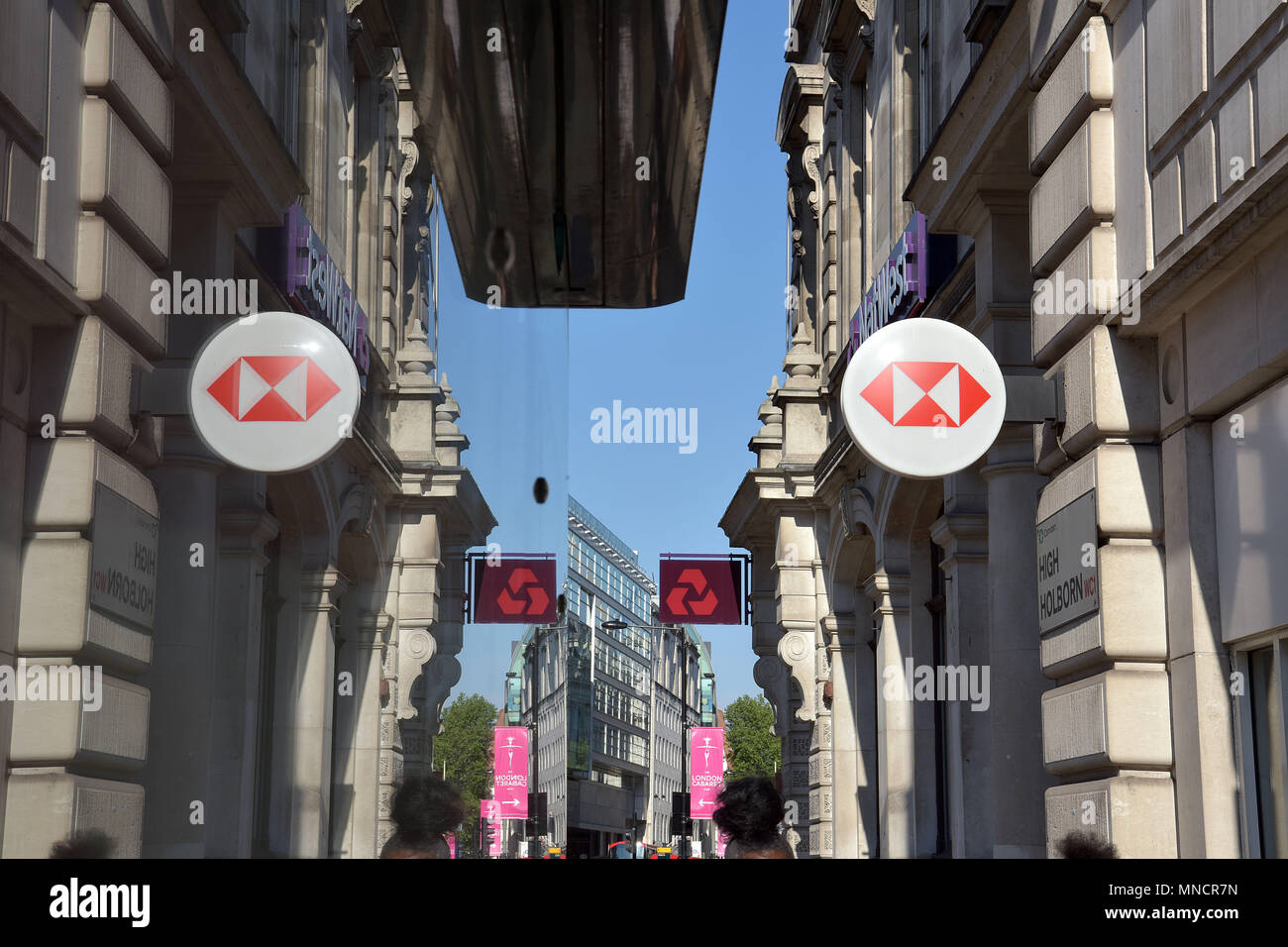 People walk past the bank branches of the HSBC and NatWest banks on High Holborn, central London. - Stock Image