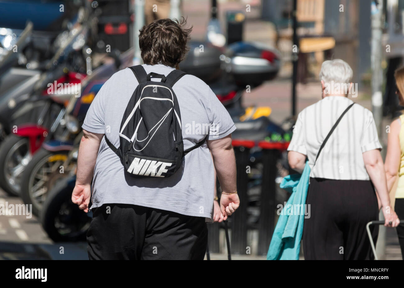 Obese man from behind walking away in the UK. Overweight concept. - Stock Image