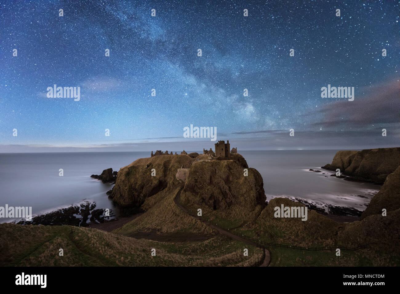 The Milky Way over Dunnottar Castle on the east coast of Scotland near Stonehaven in Aberdeenshire - Stock Image
