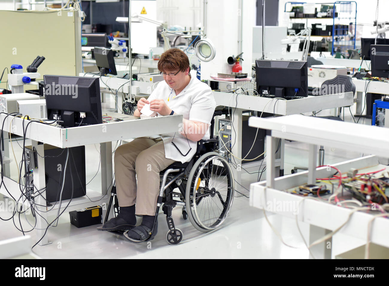 handicapped worker in a wheelchair assembling electronic components in a modern factory at the workplace - Stock Image