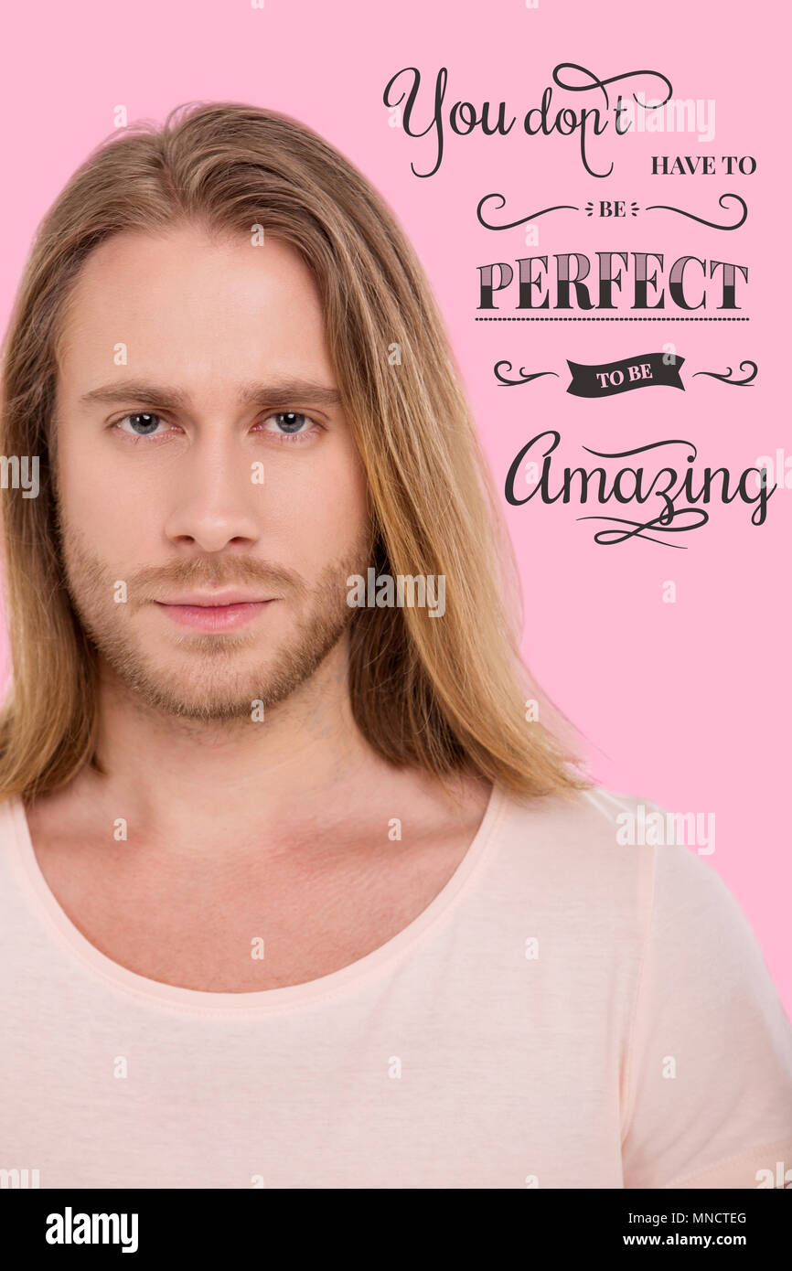 Close up of handsome light haired man against pink background - Stock Image