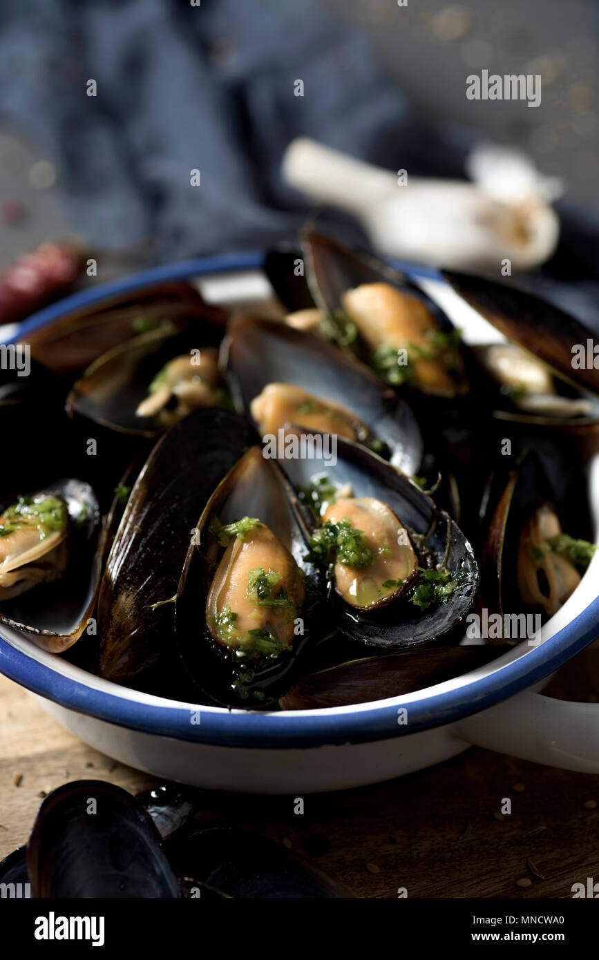 closeup of a ceramic bowl with moules mariniere, a french recipe of mussels, on a rustic wooden table - Stock Image