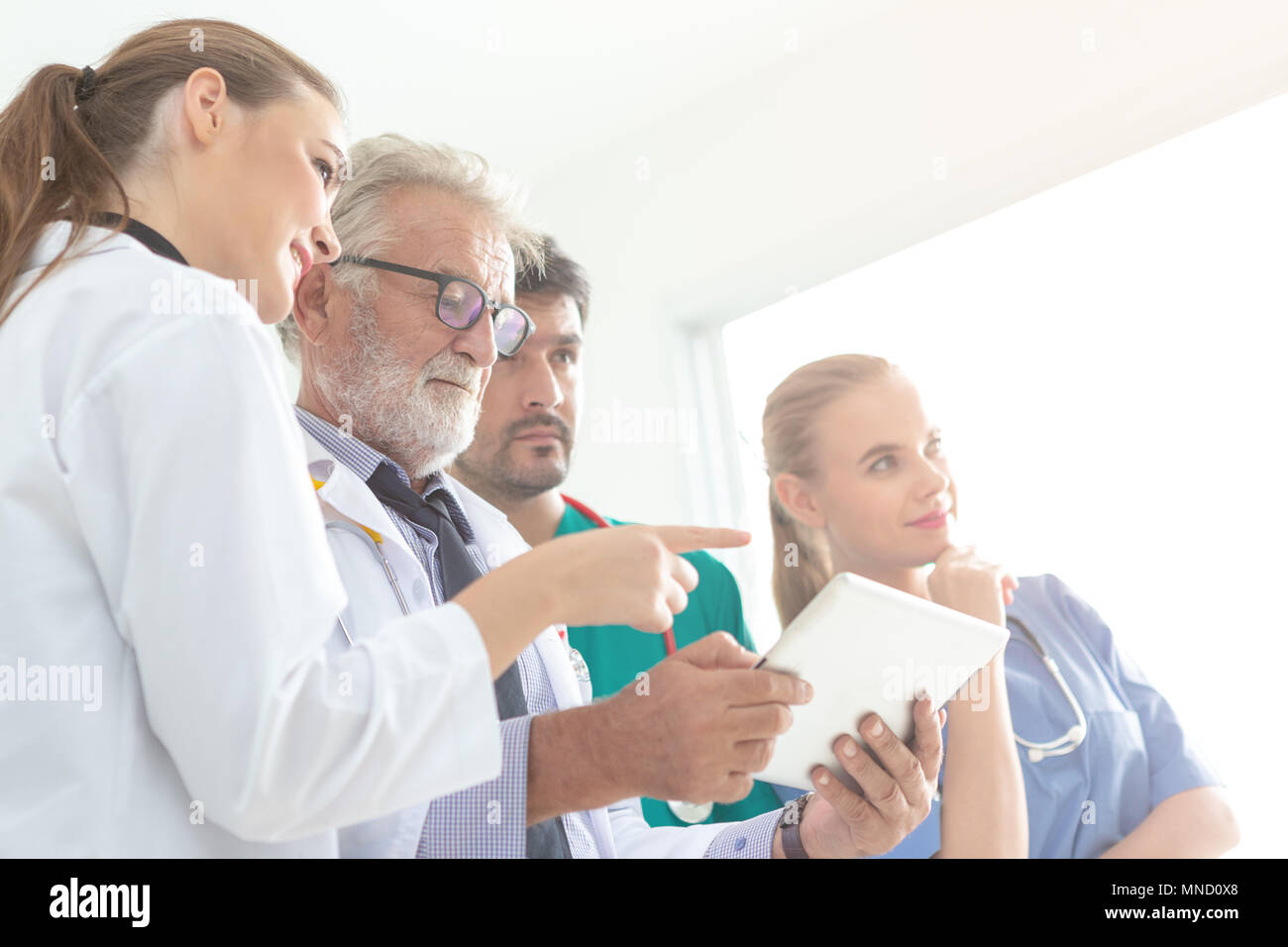 A group of doctors are using a digital tablet for discussing diagnosis and smiling while standing in front of his patient. - Stock Image