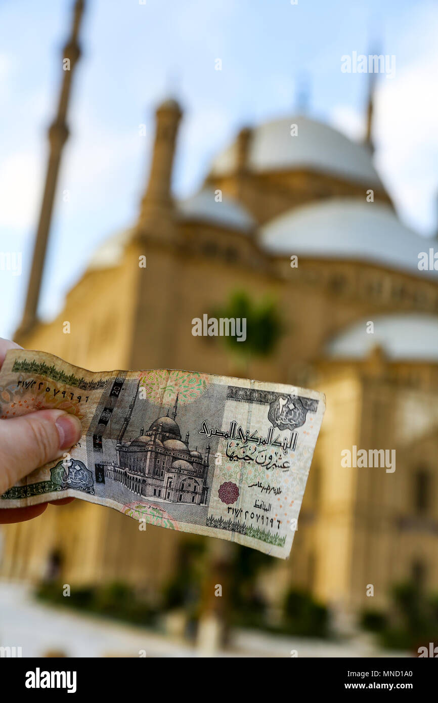 Someone holding up a 20 Egyptian Pound note showing the Great Mosque of Muhammad Ali Pasha in front of the actual mosque, Cairo, Egypt, North Africa - Stock Image