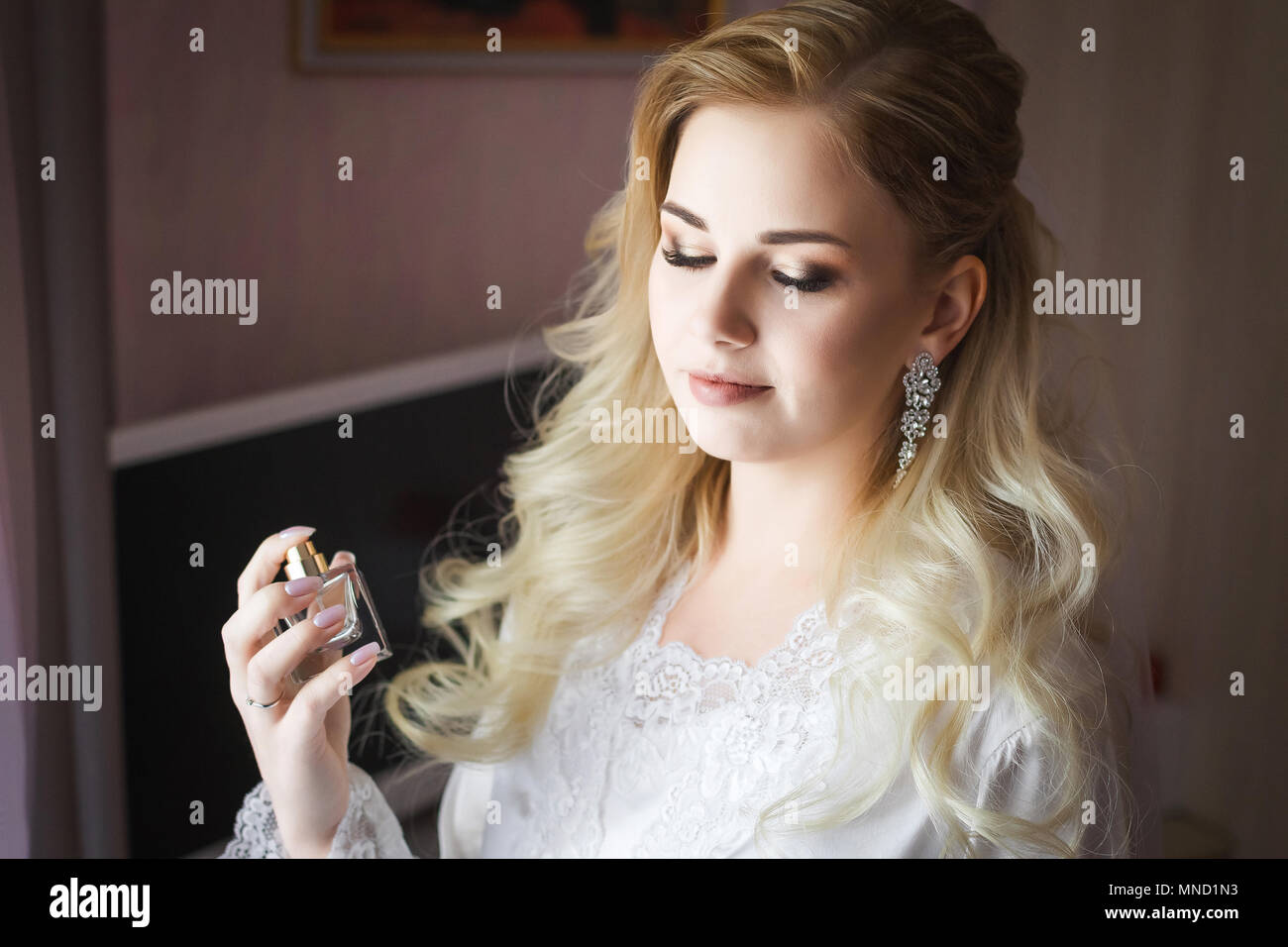 bride holding in hands a bottle of luxury perfume - Stock Image