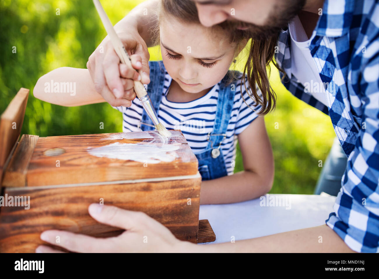 Father with a small daughter outside, making wooden birdhouse. - Stock Image