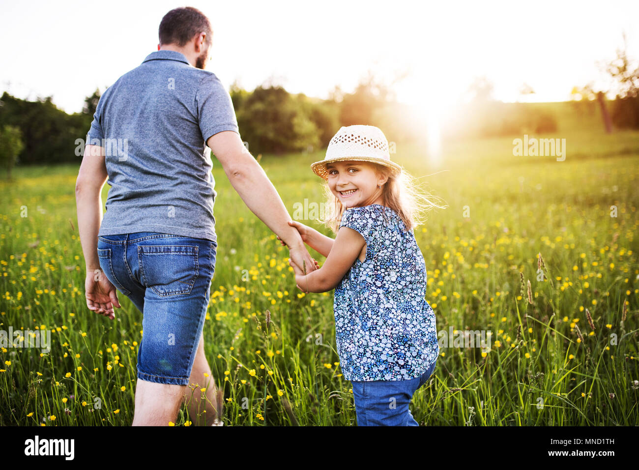 Father with a small daughter on a walk in spring nature. - Stock Image