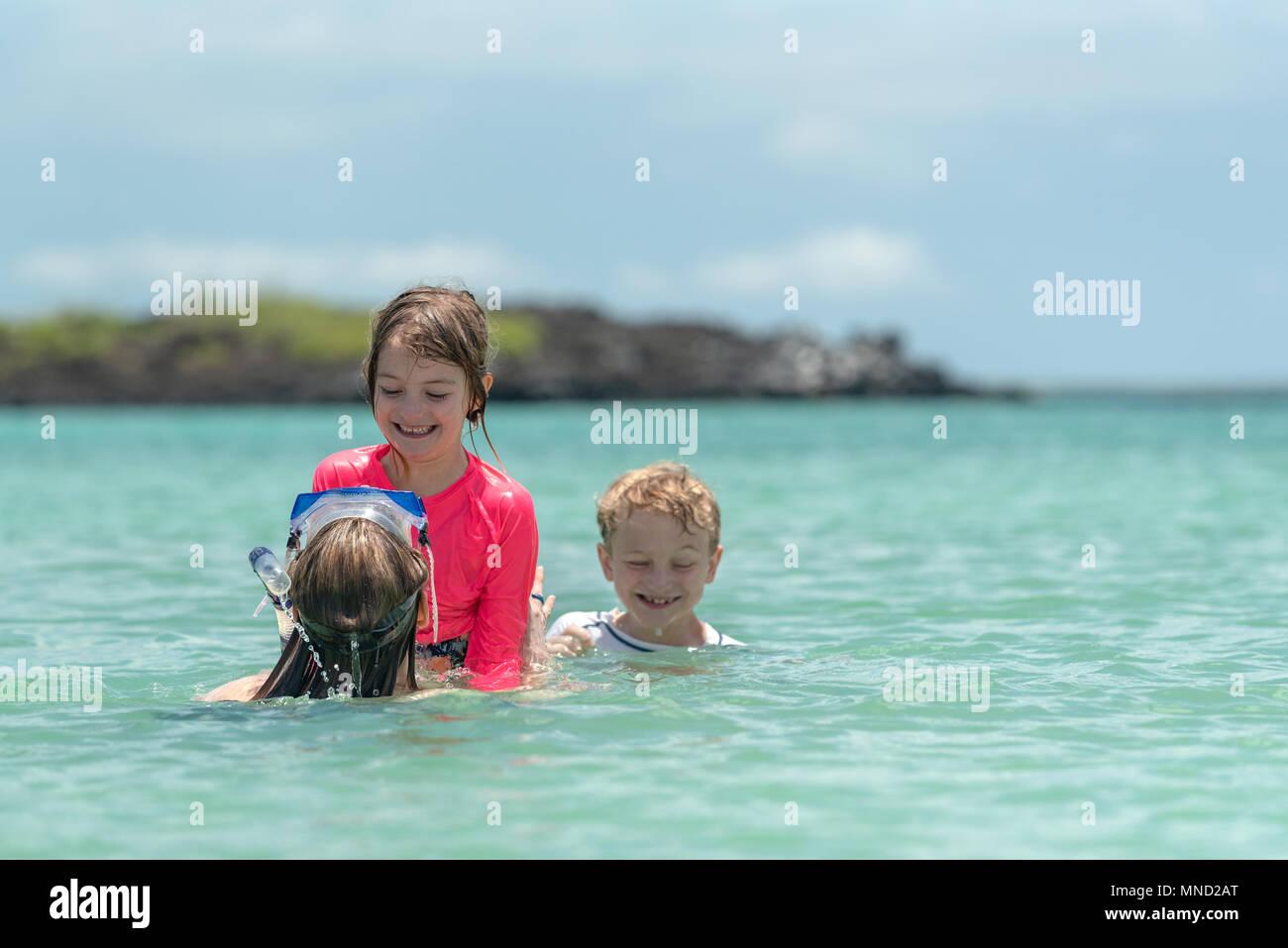f4f9f9b46b7 Mother and children enjoying the water off San Cristobal Island, Galapagos  Islands, Ecuador.