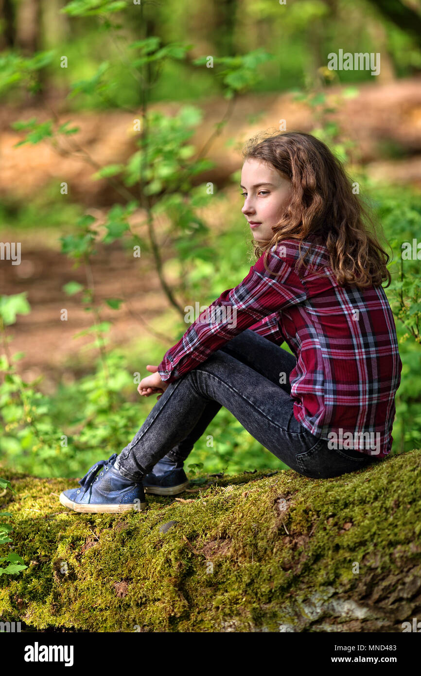 Pensive young girl is sitting in nature - Stock Image