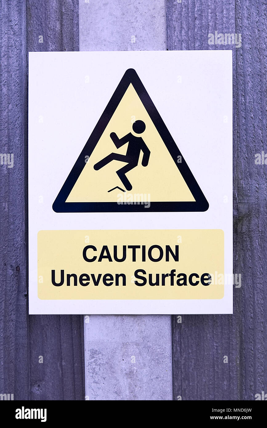 CAUTION uneven surface sign black and yellow warning triangle with man slipping and falling on wooden fence - Stock Image