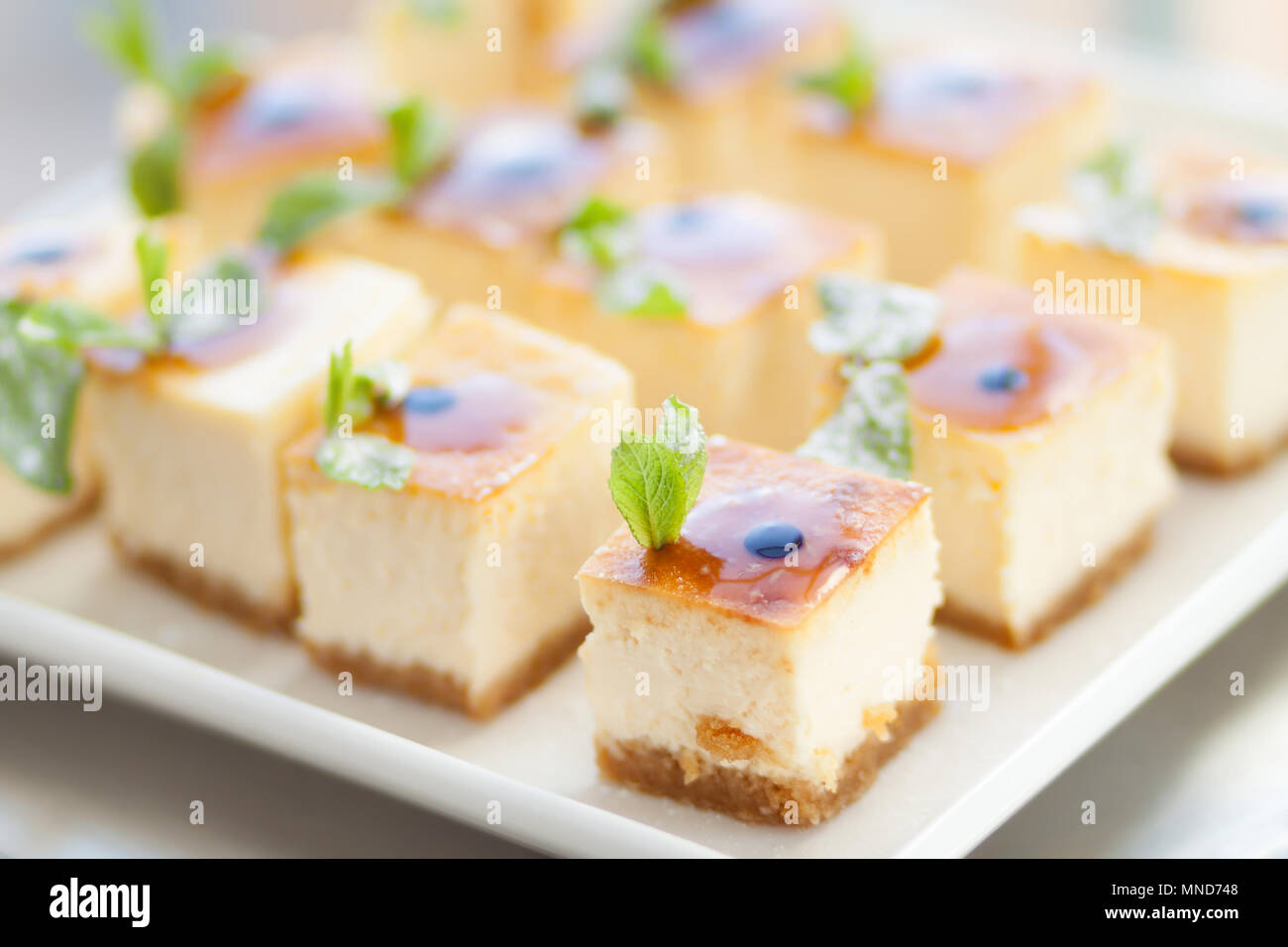 Appetizing cheesecake with mint leaves. Delicious sliced dessert on white plate. - Stock Image