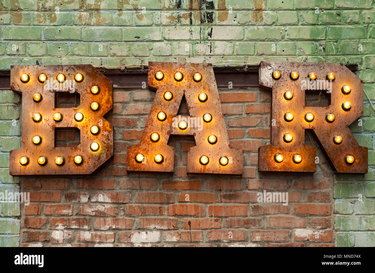 Bar signboard. Inscription from large metal letters decorated with glowing light bulbs on the brick wall - Stock Image