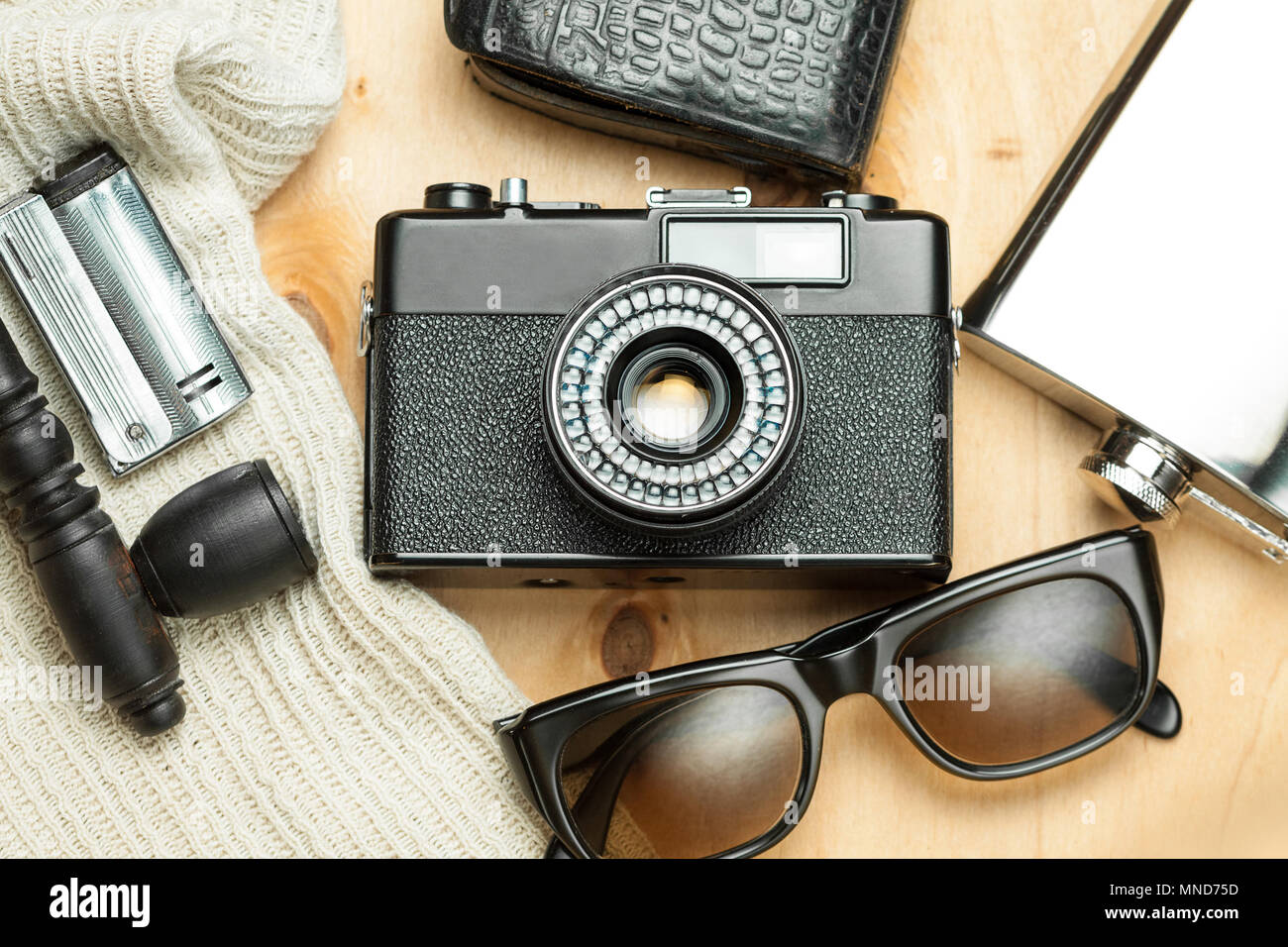 Accessories of the creative person. 35-mm film camera, exposure meter in leather case, steel flask, sunglasses and smoking set on wooden background. - Stock Image