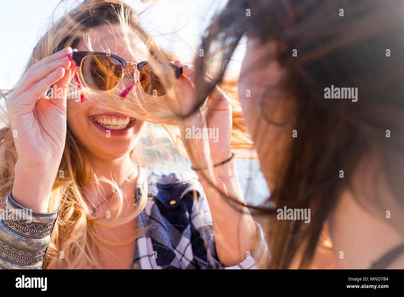 Two young beautiful woman look themselves with up eyeglass in a sunny day. Nice smile viewed from the back of a woman. Friendship between two spanish  - Stock Image