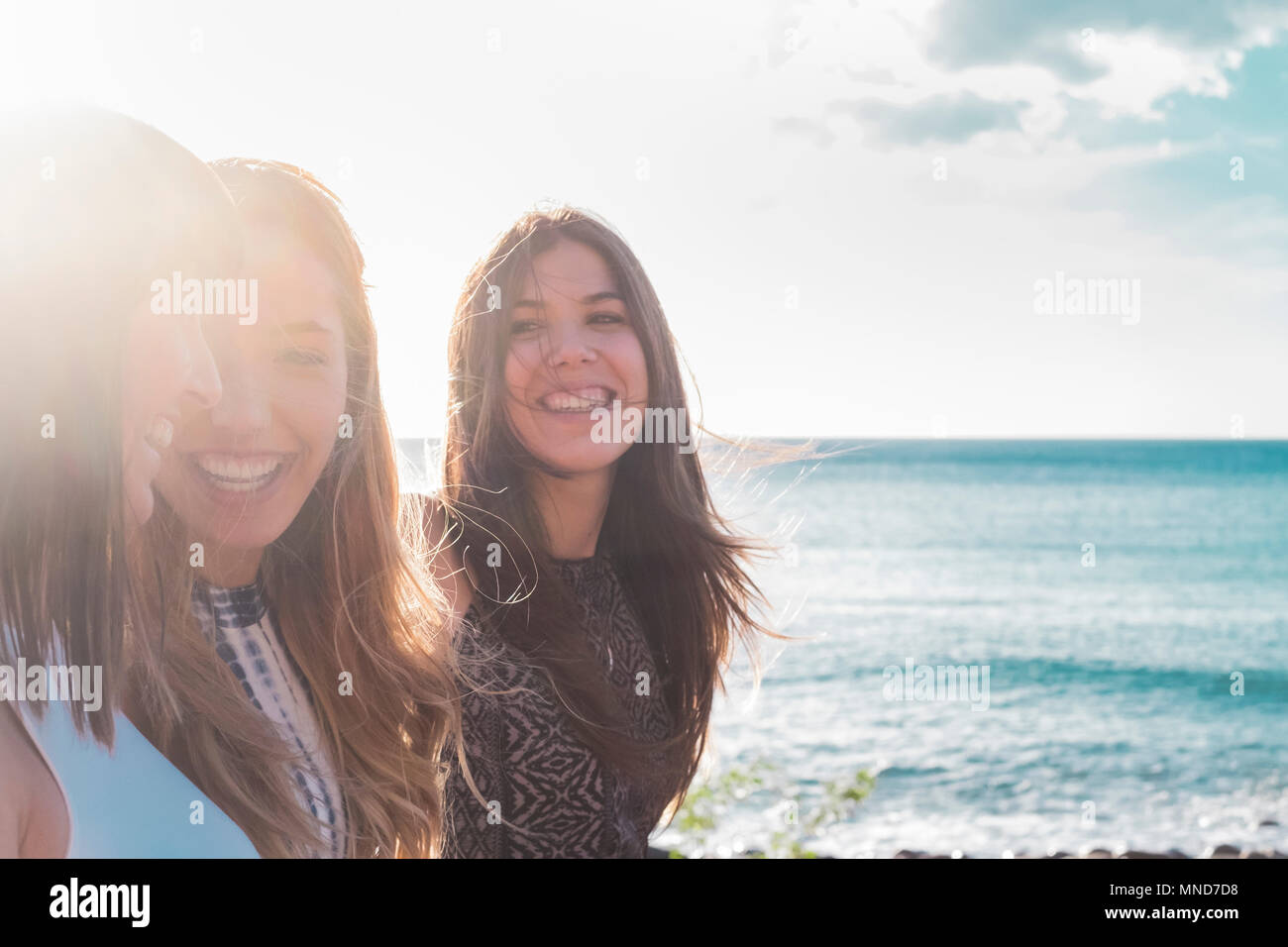 3 young women walk on the beach looking at each other, laughing and spending free time together. on a nice summer day. with sun and sea as a backgroun - Stock Image