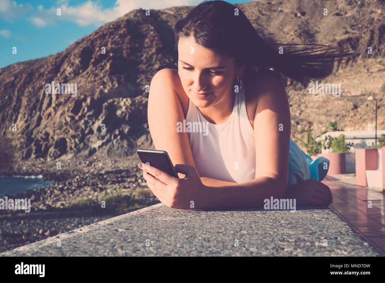 Beautiful long hair spanish woman use mobile phone to send message during a vacation in Tenerife. Lay down on a wall near the beach under a blue sky w - Stock Image
