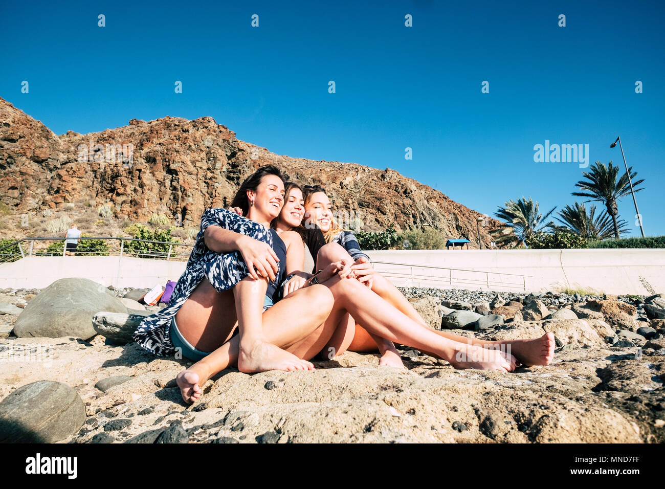 Group Of Beautiful Woman Young Speaking And Smiling Aroud In A Stone Beach In Tenerife