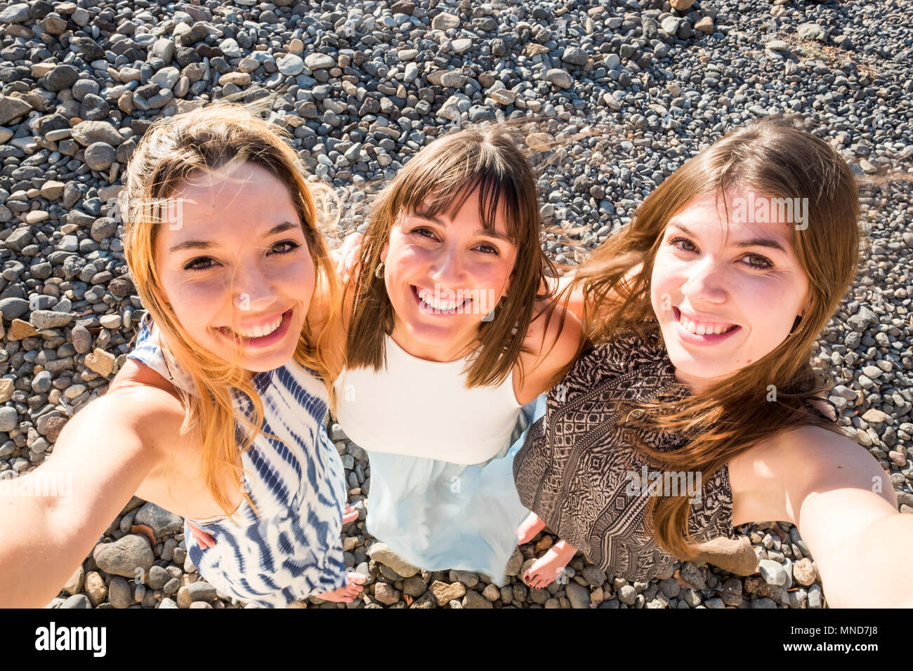 Aerial selfies for a group of three beautiful woman with a stone background. Happiness moment to catch some memories and post them on the social netwo - Stock Image