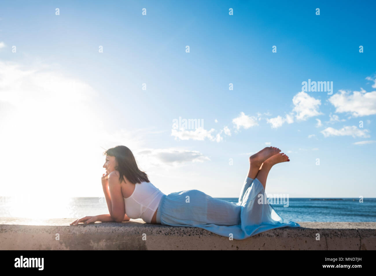 long hair spanish young woman erlaxing lay down on a wall near the beach. Sunlight on her beauty face, smile and enjoy the time. Stock Photo